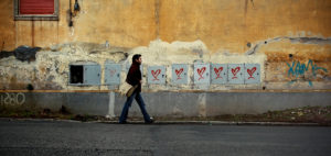 A man walking along a wall
